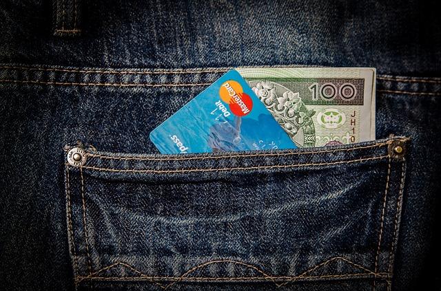 peníze s kartou v kapse